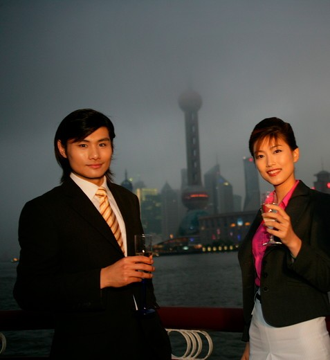 one businessman and one businesswoman smiling with wineglasses in the dusk at the Bund,Shanghai,China : Stock Photo
