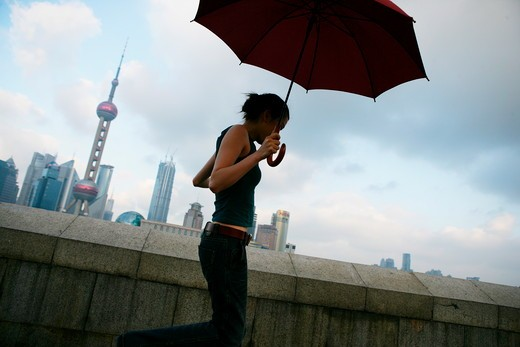 one young woman jumping with an opened umbrella at the Bund,Shanghai,China : Stock Photo