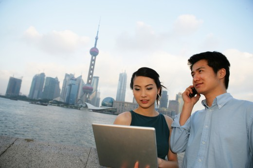 couple using laptop and on the phone at the Bund,Shanghai,China : Stock Photo
