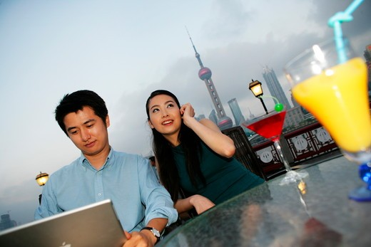 couple on the phone and using laptop beside table on the Bund,Shanghai,China : Stock Photo