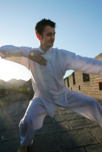 caucasian in Chinese traditional clothing practising martial arts on Great Wall,Beijing,China : Stock Photo