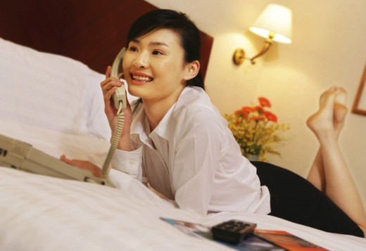 young woman on the phone on hotel bed : Stock Photo