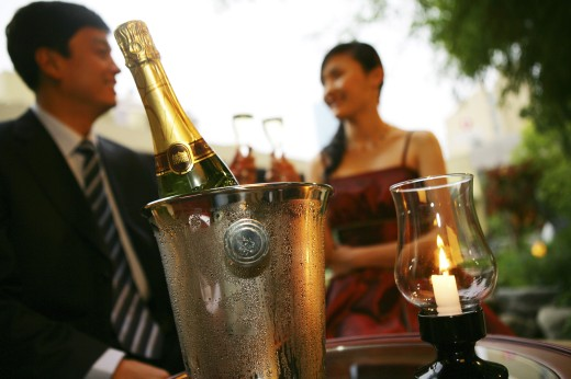 champagne flute and ice bucket,couple drinking in background : Stock Photo