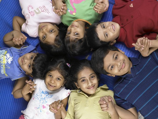 South Asian Indian boys and girls lay down on floor and holding hands in nursery school MR : Stock Photo