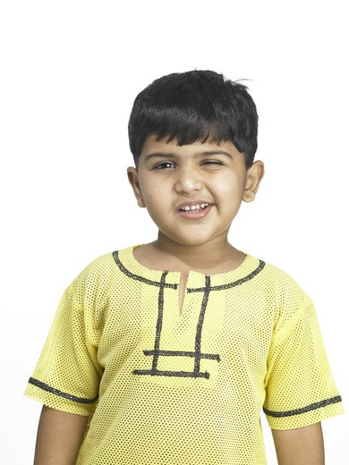 South Asian Indian boy making funny face in nursery school MR winking : Stock Photo