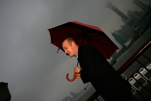 Stock Photo: 1886R-63653 one foreign businessman smiling while holding an opened umbrella at the Bund,overcast and rainy,Shanghai,China