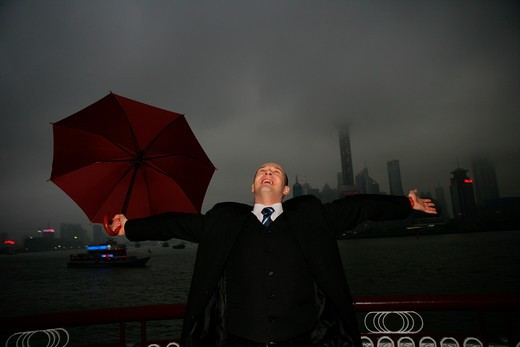 one foreign businessman arm stretched while holding an opened umbrella at the Bund,overcast and rainy,Shanghai,China : Stock Photo