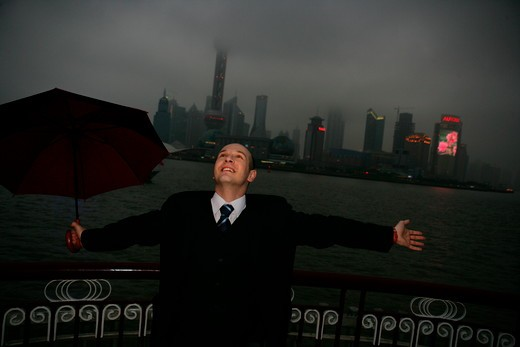 Stock Photo: 1886R-63664 one foreign businessman arm stretched while holding an opened umbrella at the Bund,overcast and rainy,Shanghai,China