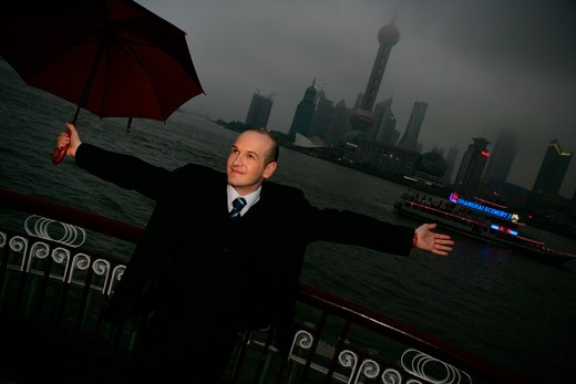 Stock Photo: 1886R-63667 one foreign businessman arm stretched while holding an opened umbrella at the Bund,overcast and rainy,Shanghai,China