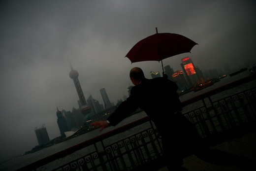 one foreign businessman jumping while holding an opened umbrella at the Bund,overcast and rainy,Shanghai,China : Stock Photo