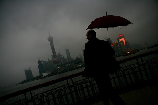 one foreign businessman smiling while holding an opened umbrella at the Bund,overcast and rainy,Shanghai,China : Stock Photo