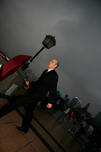 Stock Photo: 1886R-63680 one foreign businessman walking with an opened umbrella at the Bund,overcast and rainy,Shanghai,China