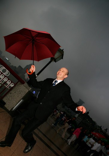 Stock Photo: 1886R-63683 one foreign businessman jumping with an opened umbrella at the Bund,overcast and rainy,Shanghai,China