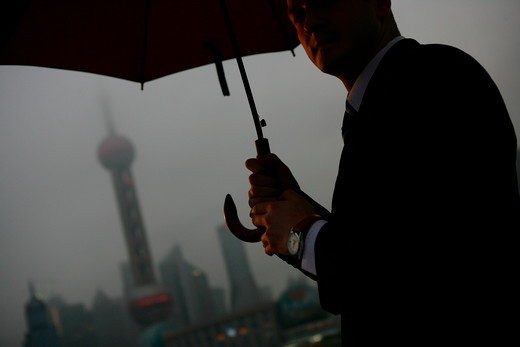 one foreign businessman standing with an opened umbrella at the Bund,overcast and rainy,Shanghai,China : Stock Photo