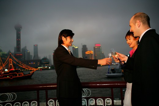 Stock Photo: 1886R-63709 two businessmen and one businesswoman from different cultures toasting in the dusk at the Bund,Shanghai,China