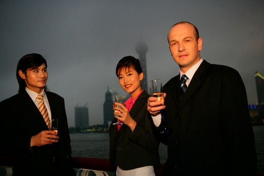 two businessmen and one businesswoman from different cultures smiling with wineglasses in the dusk at the Bund,Shanghai,China : Stock Photo