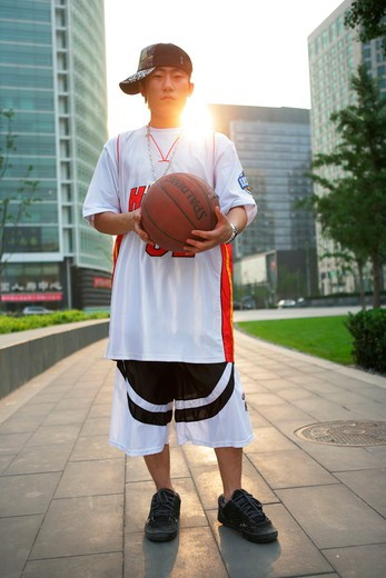 Stock Photo: 1886R-63752 young man holding basketball on square beside office buildings,Beijing,China