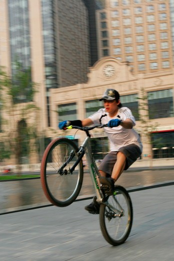 young man performing a stunt with a bicycle on square beside office buildings,Beijing,China : Stock Photo