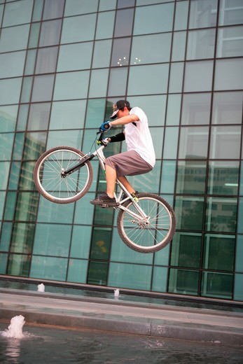 Stock Photo: 1886R-63773 young man performing a stunt with a bicycle on square beside office buildings,Beijing,China
