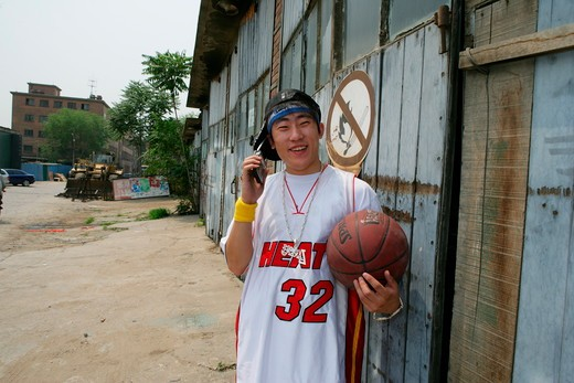 Stock Photo: 1886R-63903 young man on the phone at 798 Art Zone with baketball,Beijing,China
