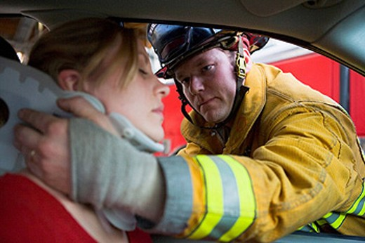 Fireman helping woman with neck brace selective focus : Stock Photo