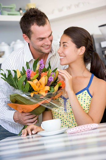 Young man giving a bouquet of flowers to a young girl sitting at a table : Stock Photo