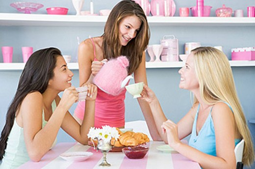Three young woman sitting at a table having tea and a snack : Stock Photo
