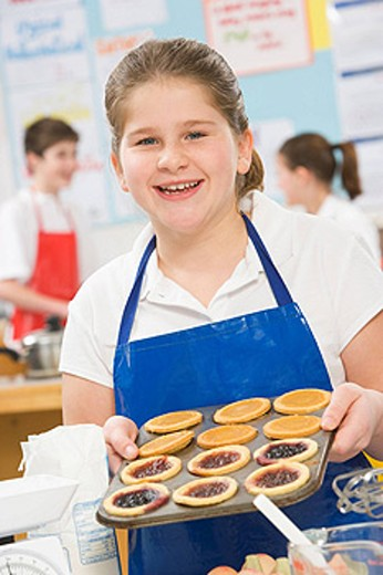 Stock Photo: 1888R-10724 Female student holding a tray of tarts in cooking class