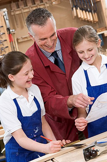 Female students reviewing woodworking plans with teacher : Stock Photo
