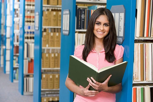 Woman in library holding book depth of field : Stock Photo
