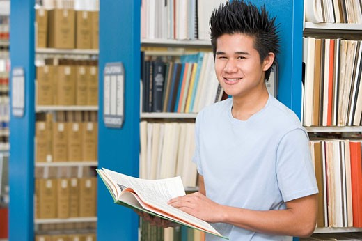 Man in library holding book depth of field : Stock Photo
