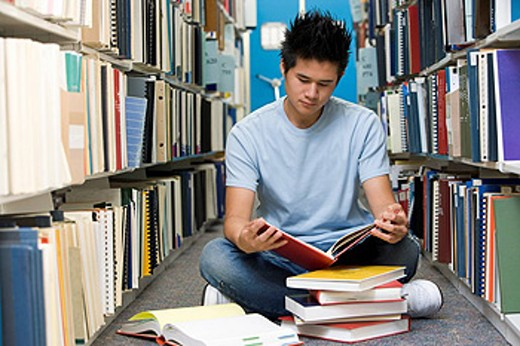 Stock Photo: 1888R-10971 Man sitting on floor in library reading book