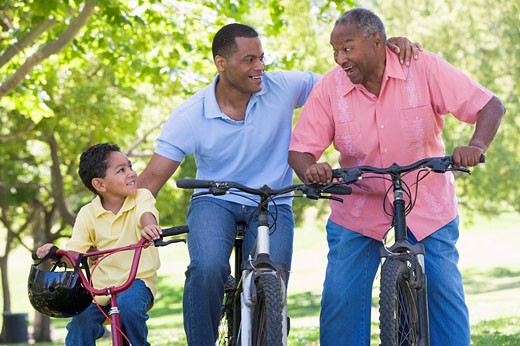 Stock Photo: 1888R-11145 Grandfather grandson and son bike riding.