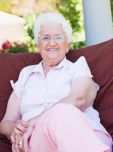 Senior woman sitting outdoors on a chair : Stock Photo