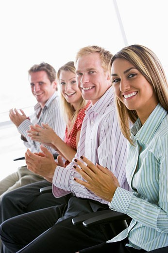 Four businesspeople applauding indoors smiling : Stock Photo