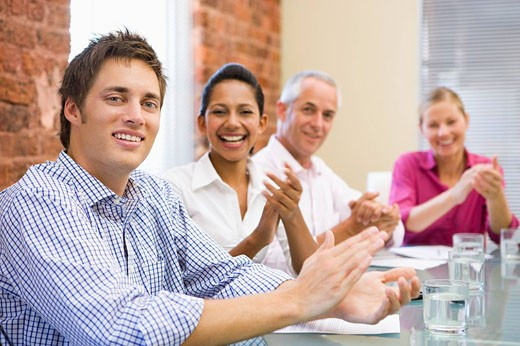 Four businesspeople in boardroom applauding and smiling : Stock Photo