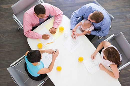Four businesspeople in boardroom with one holding a baby : Stock Photo