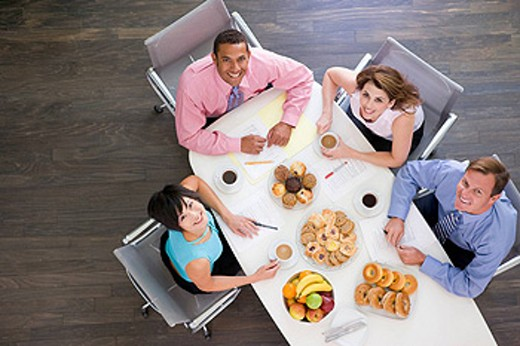 Stock Photo: 1888R-11726 Four businesspeople at boardroom table with breakfast smiling