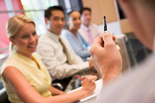 Five businesspeople at boardroom table with focus on businessman´s pen : Stock Photo