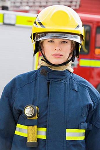 Firewoman standing by fire engine wearing helmet : Stock Photo