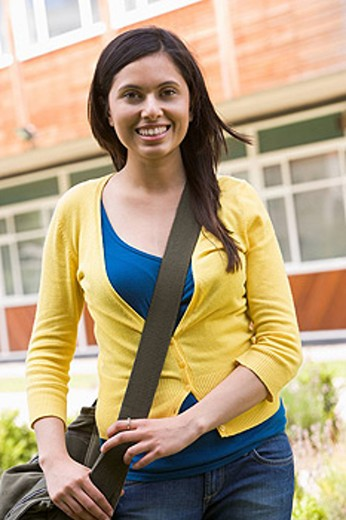 Student standing outdoors smiling : Stock Photo