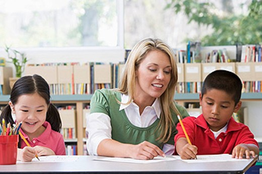Stock Photo: 1888R-12280 Two students in class writing with teacher helping