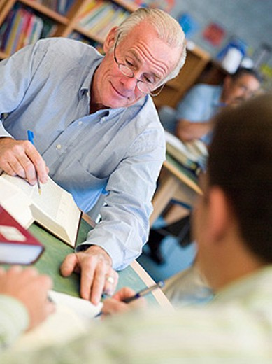 Two men in library with notepads talking selective focus : Stock Photo