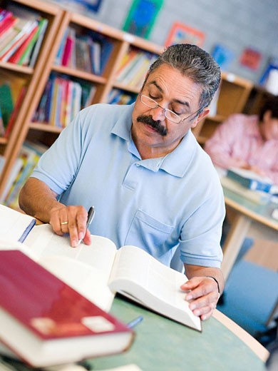 Man sitting in library with a book and notepad selective focus : Stock Photo