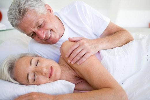 Stock Photo: 1888R-12705 Man waking woman lying in bed sleeping