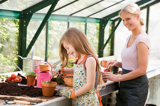 Young girl and woman in greenhouse putting soil in pots smiling : Stock Photo