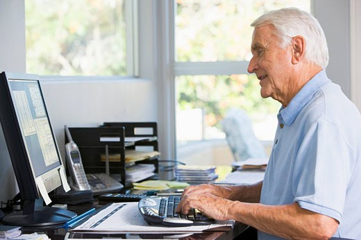 Man in home office using computer smiling : Stock Photo