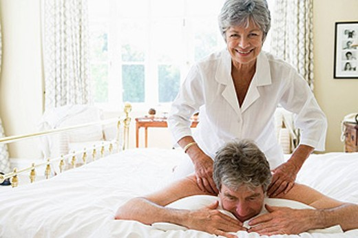 Woman giving man massage in bedroom smiling : Stock Photo