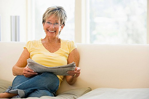 Woman in living room reading newspaper smiling : Stock Photo