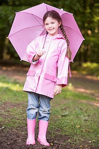 Stock Photo: 1888R-14039 Young girl outdoors with umbrella smiling